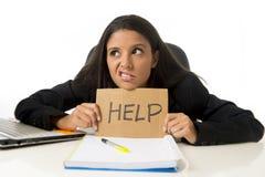 Молодой занятый отчаянный латинский знак помощи удерживания коммерсантки сидя на столе офиса в стрессе потревожился Стоковое Изображение