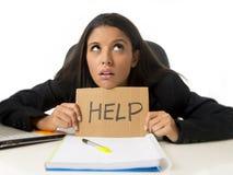 Молодой занятый отчаянный латинский знак помощи удерживания коммерсантки сидя на столе офиса в стрессе потревожился Стоковая Фотография