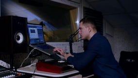 молодой звукооператор 4K в студии звукозаписи используя компьтер-книжку на смешивая столе стоковые изображения
