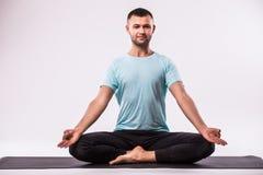 Молодой здоровый человек делает йогу изолированный над белой предпосылкой Стоковая Фотография
