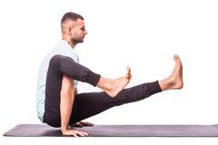 Молодой здоровый человек делает йогу над белой предпосылкой Стоковые Фотографии RF