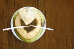Молодой здоровый cutted кокос с соломы на деревянном столе Стоковое Изображение RF