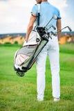 Молодой игрок в гольф держа сумку гольфа Стоковые Изображения RF