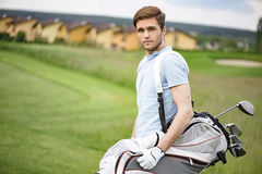 Молодой игрок в гольф держа сумку гольфа Стоковая Фотография RF