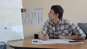 Молодой дизайнер сидит на деревянном столе и беседует на smartphone видеоматериал