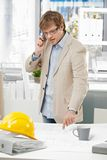 Молодой инженер говоря на телефоне указывая на план стоковое фото