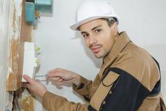 Молодой инженер построителя электрика устанавливая коробку взрывателя Стоковая Фотография RF