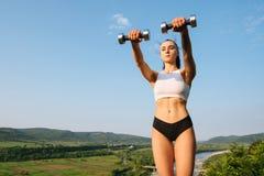 Молодой инструктор фитнеса женщины брюнет при совершенное мышечное тело делая тренировки с гантелями внешними Тренировать внутри Стоковое фото RF