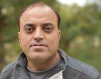 Молодой индийский человек с усмехаясь представлением Стоковое Изображение RF