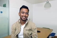 Молодой индийский человек усмехаясь на камере в его офисе Стоковое Изображение RF