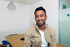 Молодой индийский человек усмехаясь на камере в его офисе Стоковые Фото