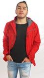 Молодой испанский человек при собранный смычок сделанный волосами нося черную футболку и красную куртку, руки в карманн брюк Стоковое Изображение
