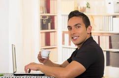 Молодой испанский человек сидя на столе держа малую чашку эспрессо и работая на белой компьтер-книжке, угле профиля Стоковые Изображения RF
