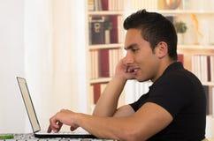 Молодой испанский человек сидя на столе работая на белой компьтер-книжке, угле профиля Стоковая Фотография