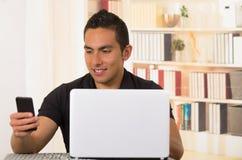 Молодой испанский человек сидя столом работая на белой компьтер-книжке и смотря мобильный телефон Стоковое Фото