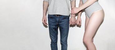 Молодой и беспечальный Красивые пары серой стеной Стоковая Фотография