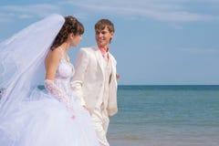Молодой и красивый жених и невеста на пляже Стоковые Изображения
