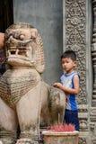 Молодой камбоджийский мальчик ждать вне виска с статуей Стоковая Фотография