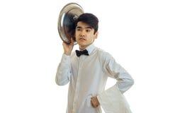 Молодой кельнер с черными волосами держит поднос около его головы и смотрит в расстояние стоковое фото rf