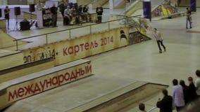 Молодой конькобежец ролика делает сальто, крены на загородке оператор смелости Конкуренция в skatepark сток-видео