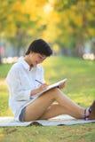 Молодой красивый азиатский текст сочинительства женщины в книге дневника в желтом цвете Стоковые Изображения