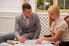 Молодой красивый архитектор обсуждая земной план Стоковое фото RF