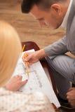 Молодой красивый архитектор обсуждая земной план Стоковые Фотографии RF