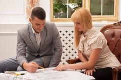 Молодой красивый архитектор обсуждая земной план Стоковая Фотография