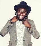 Молодой красивый афро американский мальчик в стильной шляпе битника показывать эмоциональное изолированный на белый усмехаться пр Стоковые Фото