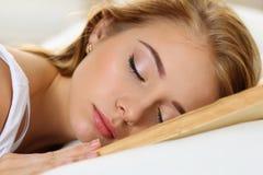 Молодой красивый белокурый портрет женщины лежа в кровати Стоковые Фото
