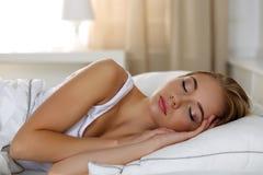 Молодой красивый белокурый портрет женщины лежа в спать кровати Стоковое Изображение RF