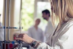 Молодой красивый белокурый химик исследователя женщины подготавливая вещества для химической пользы с блюдами лаборатории Аптекар стоковые фото