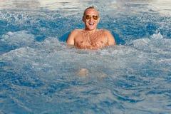 Молодой красивый белокурый человек ныряет в бассейн в лете и e Стоковые Изображения RF
