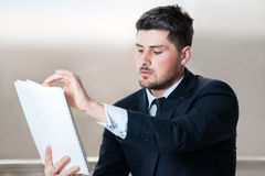 Молодой красивый бизнесмен смотря доску зажима Стоковое Фото