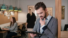 Молодой красивый бородатый человек использует таблетку сенсорного экрана в современном startup офисе Стоковое фото RF