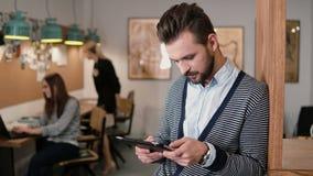 Молодой красивый бородатый человек использует таблетку сенсорного экрана в современном startup офисе Стоковые Фотографии RF