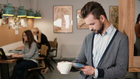 Молодой красивый бородатый человек использует таблетку сенсорного экрана и выпивая кофе в современном startup офисе Стоковые Изображения RF