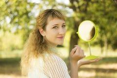 Молодой красивый взгляд девушки в зеркало в парке Зачатие нежности и нерезкости Стоковые Фотографии RF