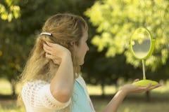 Молодой красивый взгляд девушки в зеркало в парке Зачатие нежности и нерезкости Стоковые Фото