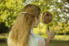 Молодой красивый взгляд девушки в зеркало в парке Зачатие нежности и нерезкости Стоковая Фотография RF