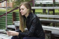 Молодой красивый взгляд девушки и слушая музыка на вашем мобильном телефоне на старых стадионах bench Стоковые Фото