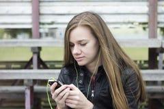 Молодой красивый взгляд девушки и слушая музыка на вашем мобильном телефоне на старых стадионах bench Стоковые Фотографии RF