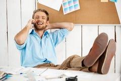 Молодой красивый жизнерадостный расслабленный усмехаясь уверенно бизнесмен сидя на таблице при ноги вверх говоря на телефоне бело Стоковое фото RF