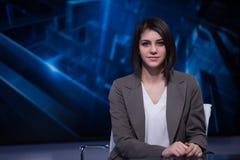 Молодой красивый диктор телевидения брюнет на студии во время широковещания в реальном маштабе времени Женский директор ТВ на ред стоковые фотографии rf