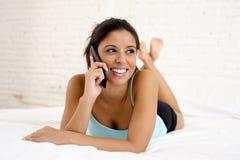 Молодой красивый испанский говорить женщины ослабил на мобильном телефоне в кровати Стоковое Изображение RF