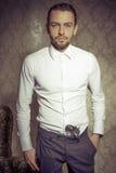 Молодой красивый и элегантный человек представляя с оружием в его брюках изолированных над винтажной предпосылкой стоковые фотографии rf