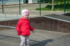 Молодой красивый младенец девушки в красной куртке и белая шляпа играя на спортивной площадке в коньке паркуют, усмехаясь и имея  Стоковое Фото