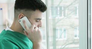 молодой красивый доктор 4K в зеленой форме говоря на мобильном телефоне видеоматериал