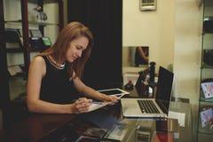 Молодой красивый документ бумаг чтения коммерсантки или предпринимателя во время работы на портативном компьютере пока стоящ в ее Стоковые Изображения