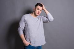 Молодой красивый портрет человека на предпосылке серого цвета студии Стоковое фото RF